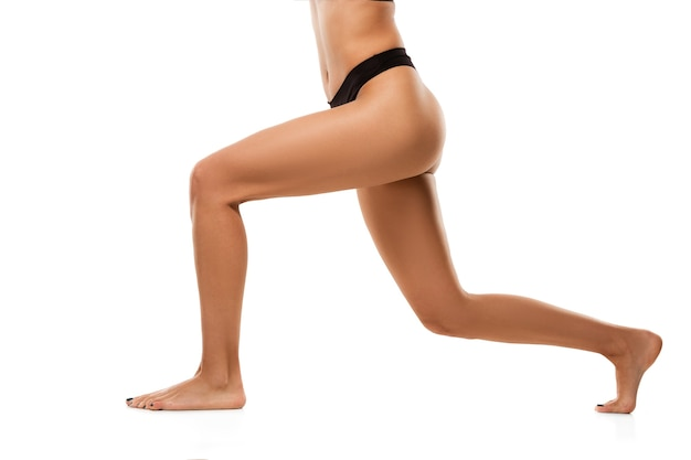 Belle gambe femminili, glutei e pancia isolati su muro bianco