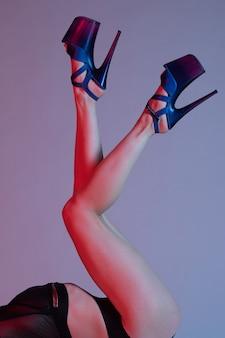 Красивые женские ножки в синих туфлях на высоких каблуках для танцев на пилоне.