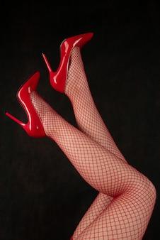 망사 스타킹과 빨간 신발에 아름다운 여성 다리