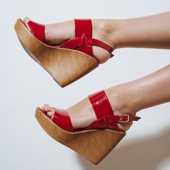 くさびの赤いサンダルで美しい女性の脚