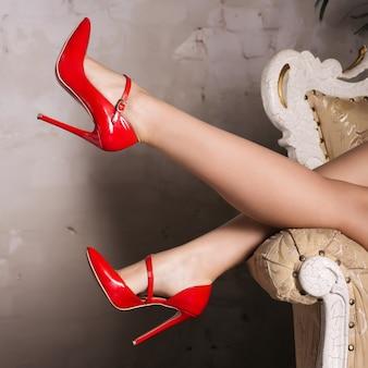赤いスタイリッシュなハイヒールの靴で美しい女性の脚