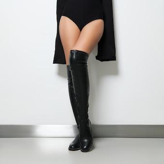 Beautiful female legs in overknee boots posing near the wall