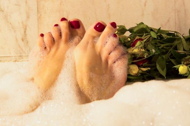 스파에서 빨간 페디큐어와 함께 아름 다운 여성 다리. 여성 발의 두 번째 발가락이 첫 번째 비표준 다리보다 큽니다.
