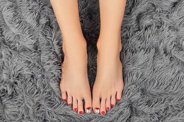 Красивые женские ножки с новогодним дизайном ногтей на сером пушистом фоне