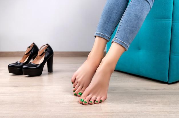 Красивые женские ножки с зеленым модным дизайном ногтей