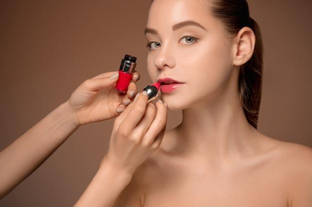 메이크업과 브러시로 아름다운 여성 입술