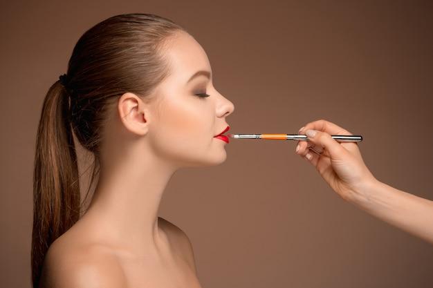 メイクとブラシで美しい女性の唇