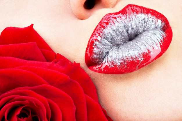 Beautiful female lips with shiny red gloss lipstick and rose