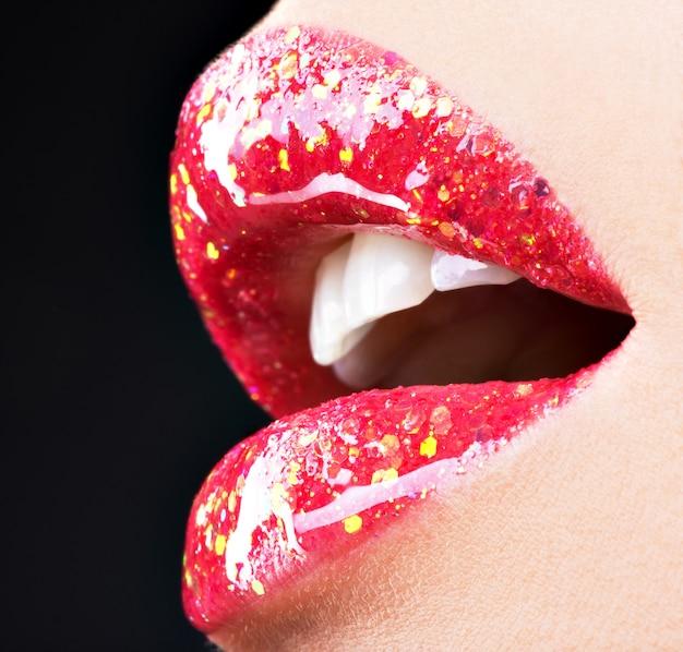 빛나는 붉은 광택 립스틱으로 아름다운 여성 입술