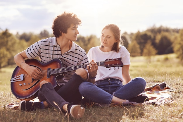 Beautiful female looks with love and happiness at her boyfriend who plays guitar and sings romantic songs to lover, have unforgettable date outdoor, enjoy togetherness. people, love, relations