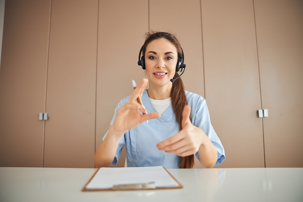 Beautiful female medic wearing headset and gesturing with her hands