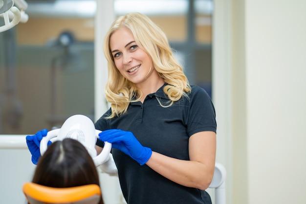 プロの機器を備えた歯科医院で歯のホワイトニングを宣伝する美しい女性モデル。