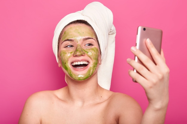 Beautiful female model has cucumber mask on face, wrapped in white towel, poses half naked, taking selfie on smartphone, posing with toothy smile, isolated on pink. cosmetology concept.