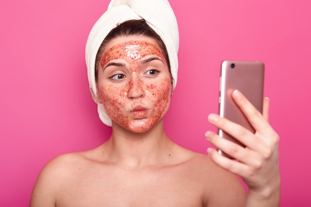 Beautiful female model has scrub mask on face, wrapped in towel, poses half naked, taking selfie on smartphone, isolated on pink, feels emotional, keeps lips rounded. cosmetology concept