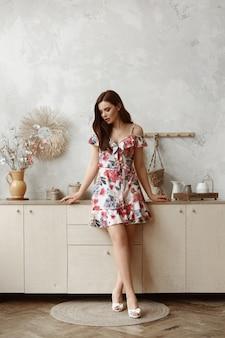 短い夏のドレスの美しい女性モデルは、居心地の良いインテリアのキッチンに立っています