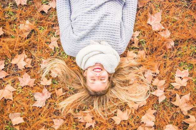 Beautiful female model laying on autumn grass