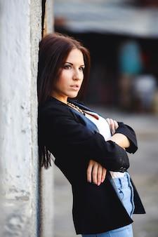 벽에 포즈를 취하는 아름 다운 여성 모델