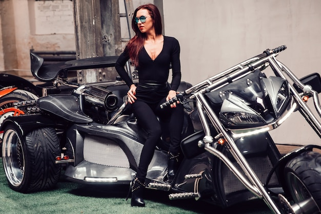 멋진 오토바이에 앉아 포즈를 취하는 아름 다운 여성 모델. 복사 공간 사진