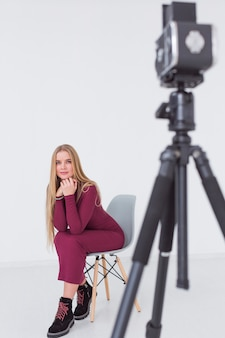 Beautiful female model sitting on a chair in studio and camera