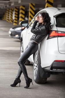 革の服でセクシーなポーズで白い車に立っている美しい女性モデル