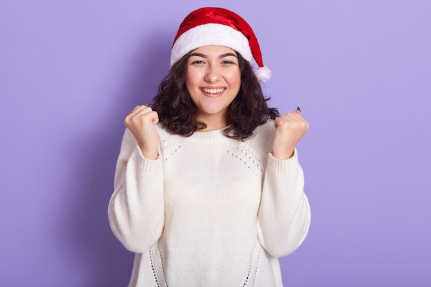 Красивая женская модель в красном санта-клаусе и белом свитере
