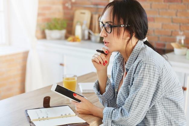 カジュアルな服装で、暗いポニーの尾を持つ美しい女性モデルは、現代のデジタルタブレットを使用し、