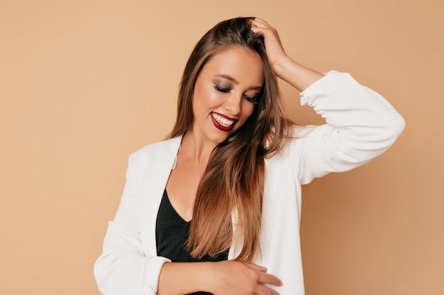 長い茶色の髪とつるの唇が素敵な笑顔で孤立した壁でポーズ美しい女性モデル。完璧な肌のクローズアップと手入れの行き届いた少女の肖像画
