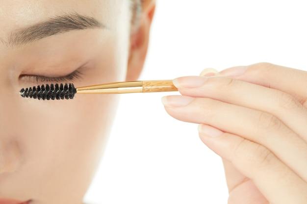 美しい女性モデルはまつげと眉毛のケアを行います