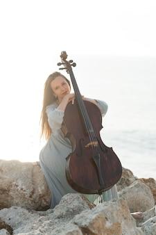 屋外でチェロでポーズをとる美しい女性ミュージシャン