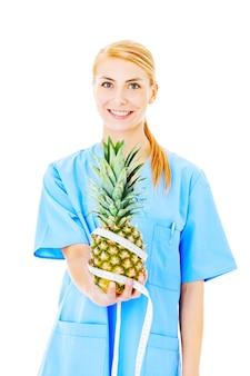 白い背景の上に分離された巻尺で包まれたパイナップルを保持している美しい女性看護師