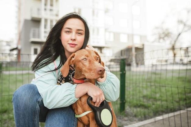 美しい女性の所有者は、かわいい茶色の品種の犬magyar vizslaを抱擁し、カメラに見えます