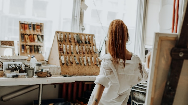 Beautiful female painter wearing white shirt dancing while painting in art workshop. selective focus. vintage style photo