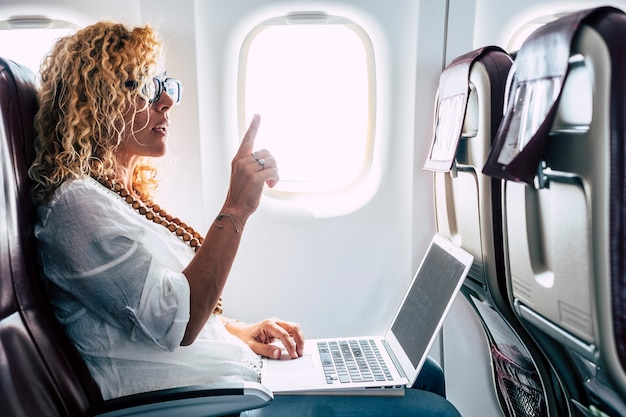 Beautiful female passeger of airplane use personal laptop computer on board with wifi internet connection and ask for hostess help