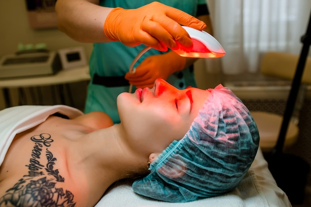 Beautiful female patient is getting a face skin treatment while lying.