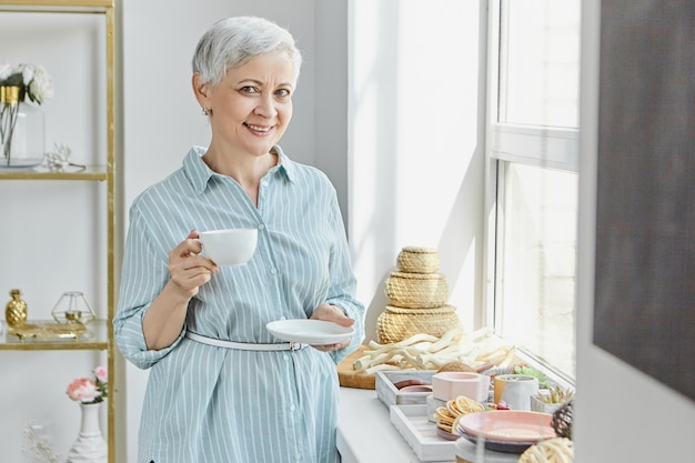 受け皿とマグカップを保持し、お茶を飲み、窓辺に食べ物や装飾を施したスタイリッシュなインテリアでポーズをとる夏の縞模様のドレスの美しい女性年金受給者。朝食を楽しむ成熟した女性