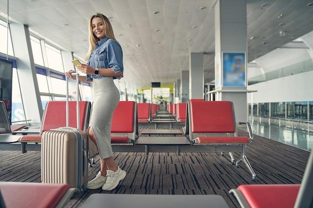 スーツケースの近くにセミポジションで立っている間、彼女の顔に笑顔を保つ美しい女性