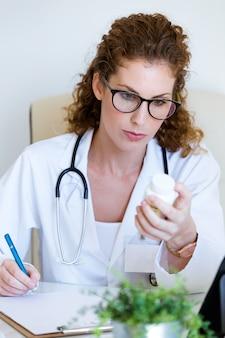 美しい女性薬剤師は、オフィスで手に薬の瓶を持っています。