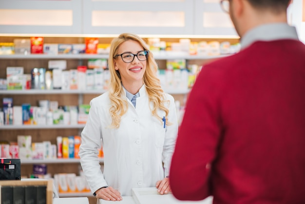 Beautiful female pharmacist talking with a male client.