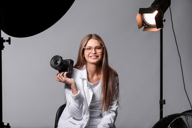 Красивая женщина-фотограф в студии