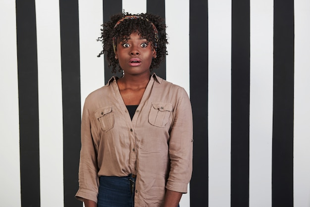 Beautiful female portrait on the black and blue stripes type background. african american girl makes shocked face