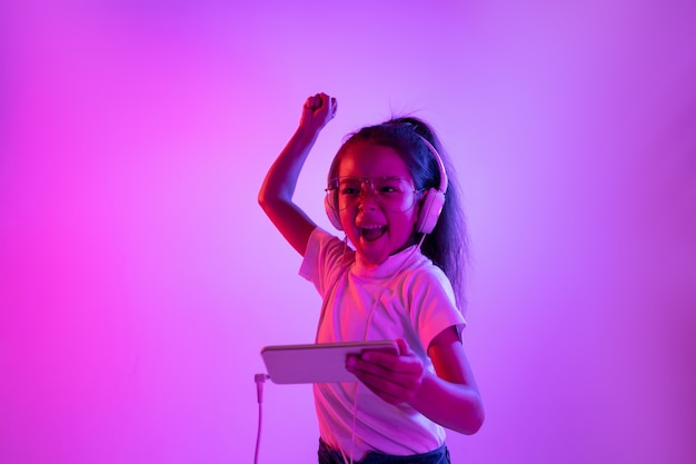 ネオンの光の中で紫色の背景に分離された美しい女性の肖像画。眼鏡の感情的な女の子。人間の感情、顔の表情の概念。ダンス、音楽鑑賞、ゲーム、そして勝利。