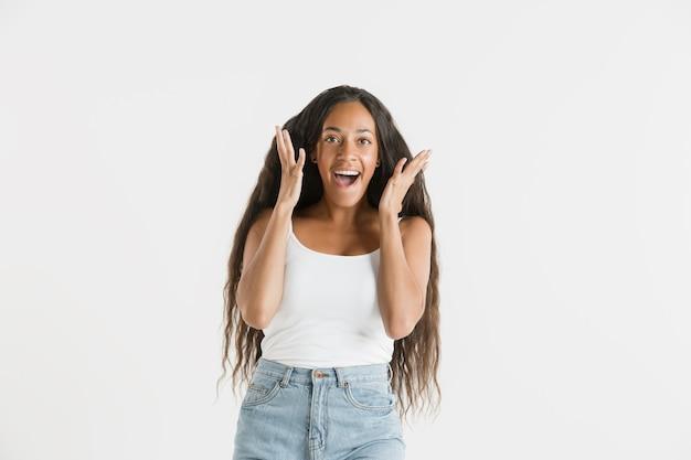 孤立した美しい女性の肖像画。長い髪の若い感情的なアフリカ系アメリカ人の女性。顔の表情、人間の感情の概念。びっくり、興奮。