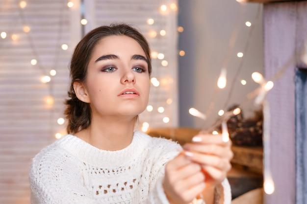 花輪とボケの白いセーターの少女の美しい女性の肖像画。