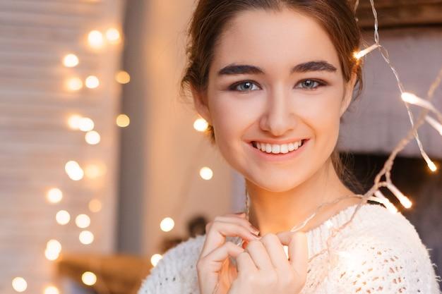 Красивый женский портрет молодой девушки в белом свитере на гирляндах и боке.