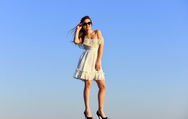 美しい女性。サングラスをかけたかなり若い美しい女性。夏の装い。美しい少女の肖像画。ビーチファッションスタイル。夏のアウトドアライフスタイル。青い空の上でポーズをとって幸せな若い女性。