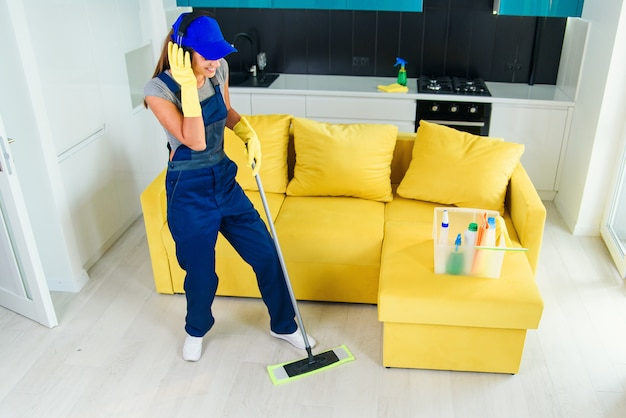 Beautiful female professional cleaner in special uniform with headphones washing the floor with mop and listens to music at apartment. housework and housekeeping concept.
