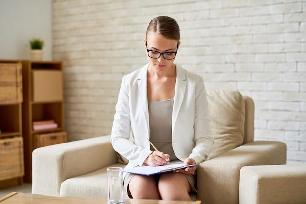 Beautiful female psychiatrist making notes