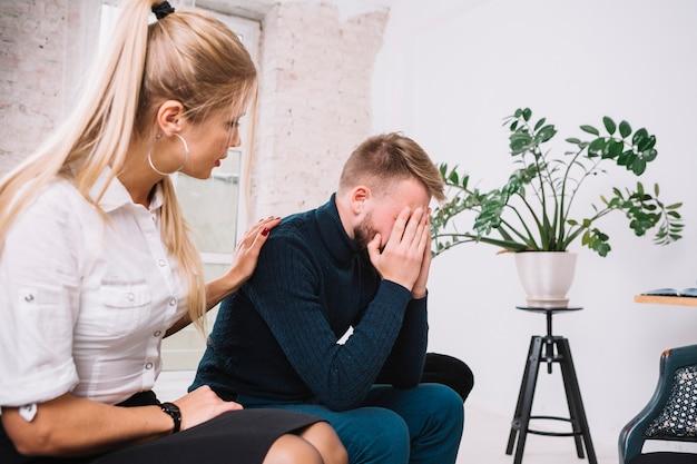 Красивый женский психолог утешая ее пациента депрессии мужского пола в клинике