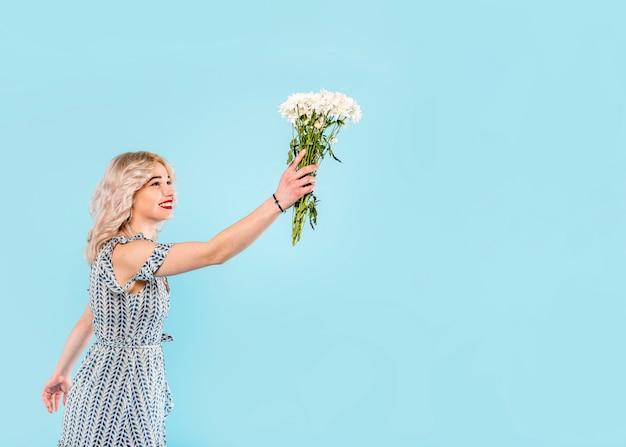 Beautiful female raising bouquet of flowers