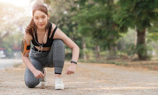 Красивая бегунья, завязывающая шнурки для обуви, готовится к бегу.